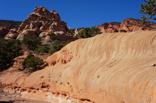 Curvy Wingate sandstone, with the rocky monolith beyond, Red Canyon Route, Capitol Reef National Park